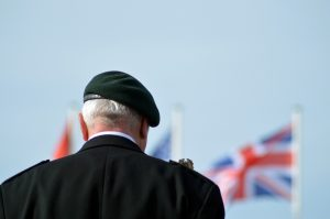 Veterans' Gateway - the first point of contact for veterans seeking support - man standing in front of flag wearing military uniform