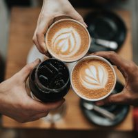Three outstretched hands holding coffee cups