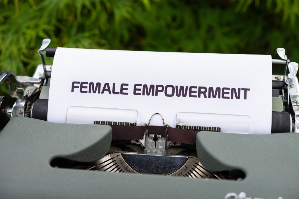 "A typewriter with piece of paper which has the words ""female empowerment"""