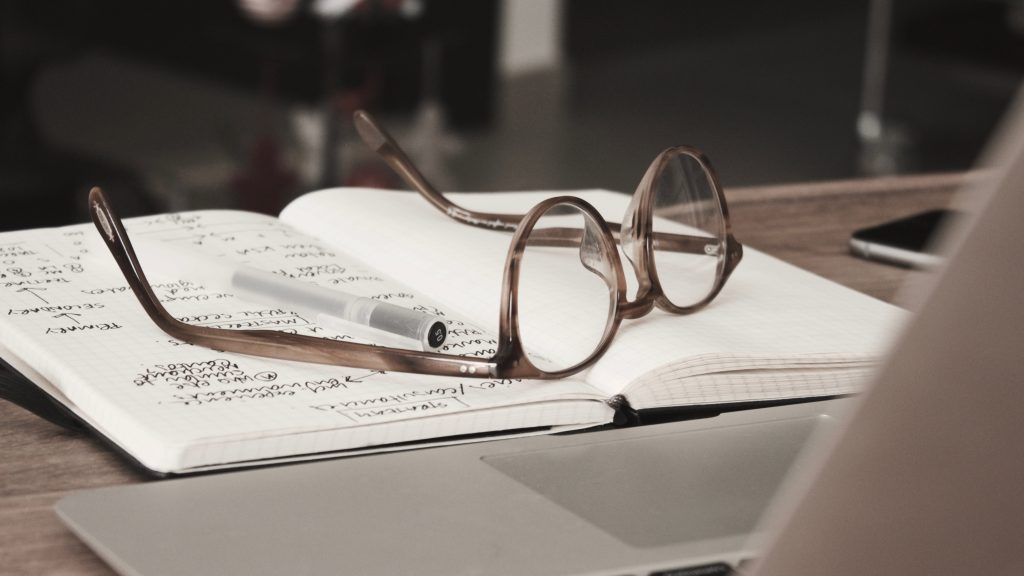 Notepad with glasses on top
